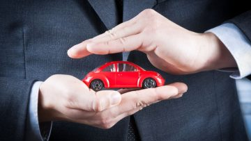 24896291 - businessman protect with his hands a red car on white table, concept for insurance, buying, renting, fuel or service and repair costs